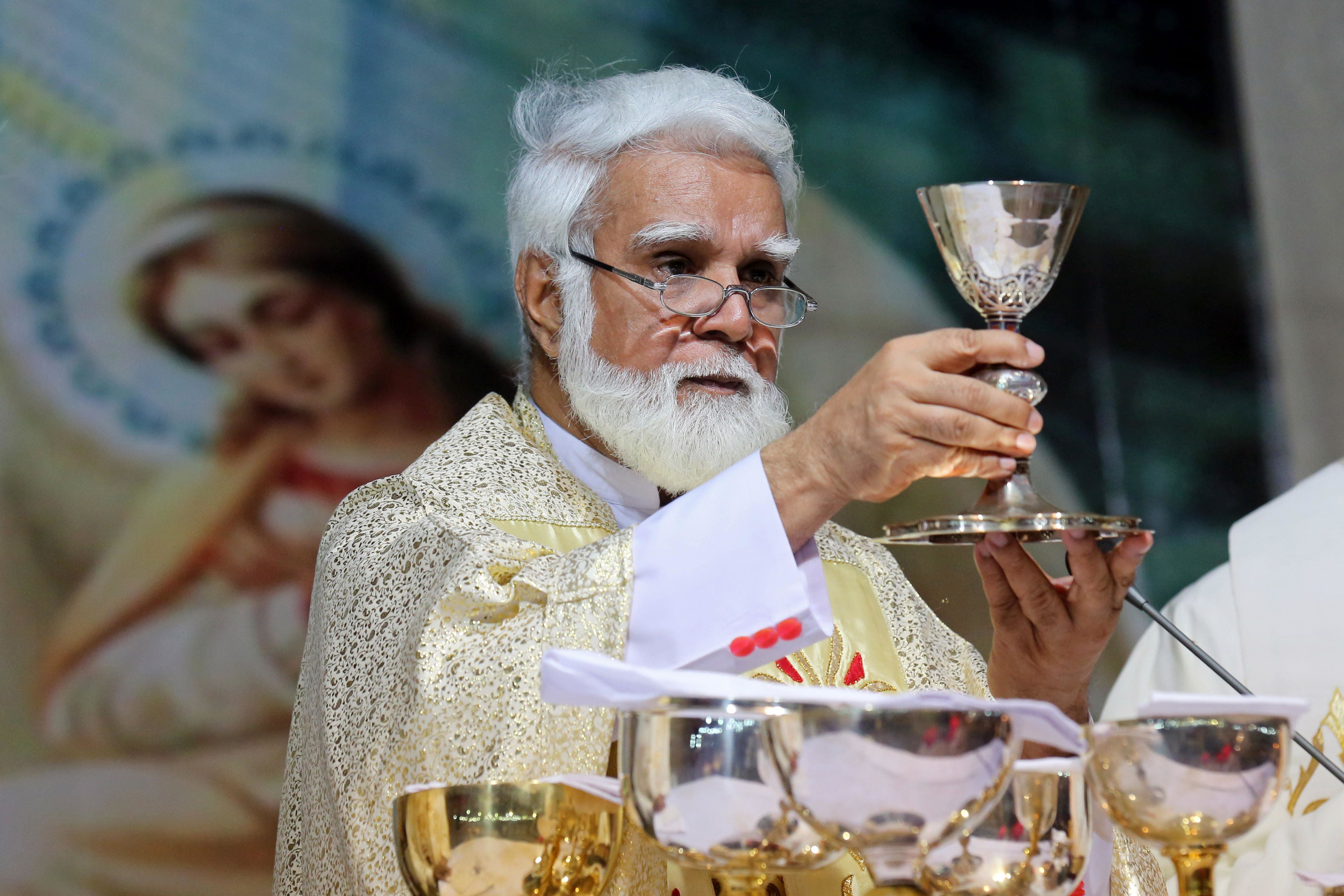 E8G78N JOSEPH COUTTS, Archbishop of the roman catholic Diocese of Karachi, Pakistan. Raising the goblet with wine/blood during the mass