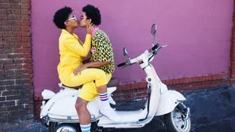A young couple wearing yellow outfits sitting on a scooter kissing