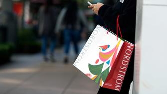 A shopper holds a Nordstrom Inc. bag while checking a mobile device at The Grove in Los Angeles, California, U.S., on Friday, Dec. 22, 2017. Christmas week last year was the biggest sales week of the season, above even Black Friday's Thanksgiving week, according to the National Retail Federation. Photographer: Dania Maxwell/Bloomberg