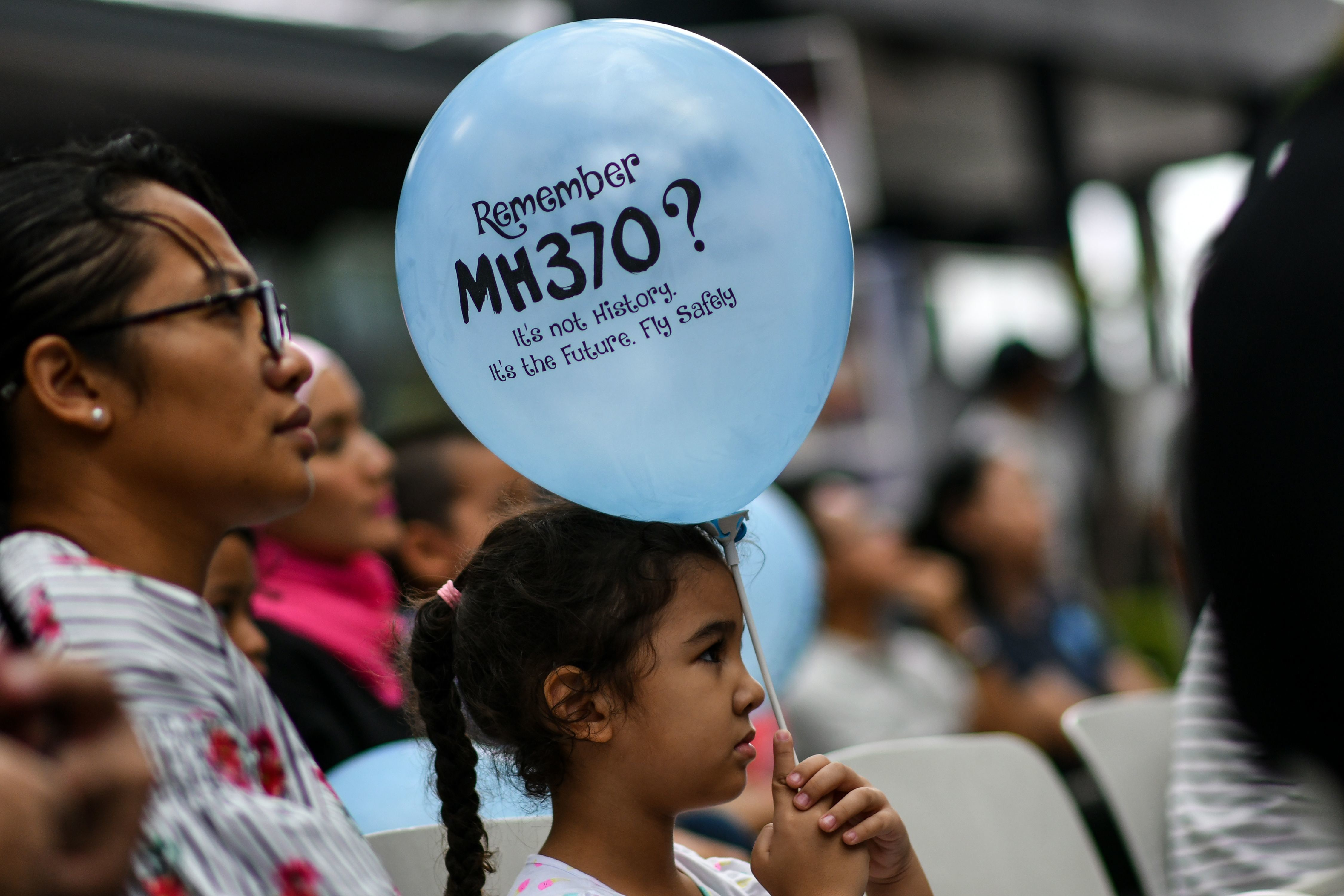 A young girl holds a balloon with a message during a memorial event for the missing Malaysia Airlines flight MH370.