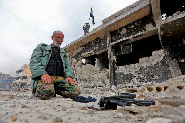 Un membre des forces armées syriennes prie dans le quartier détruit de Hajar al Aswad au...