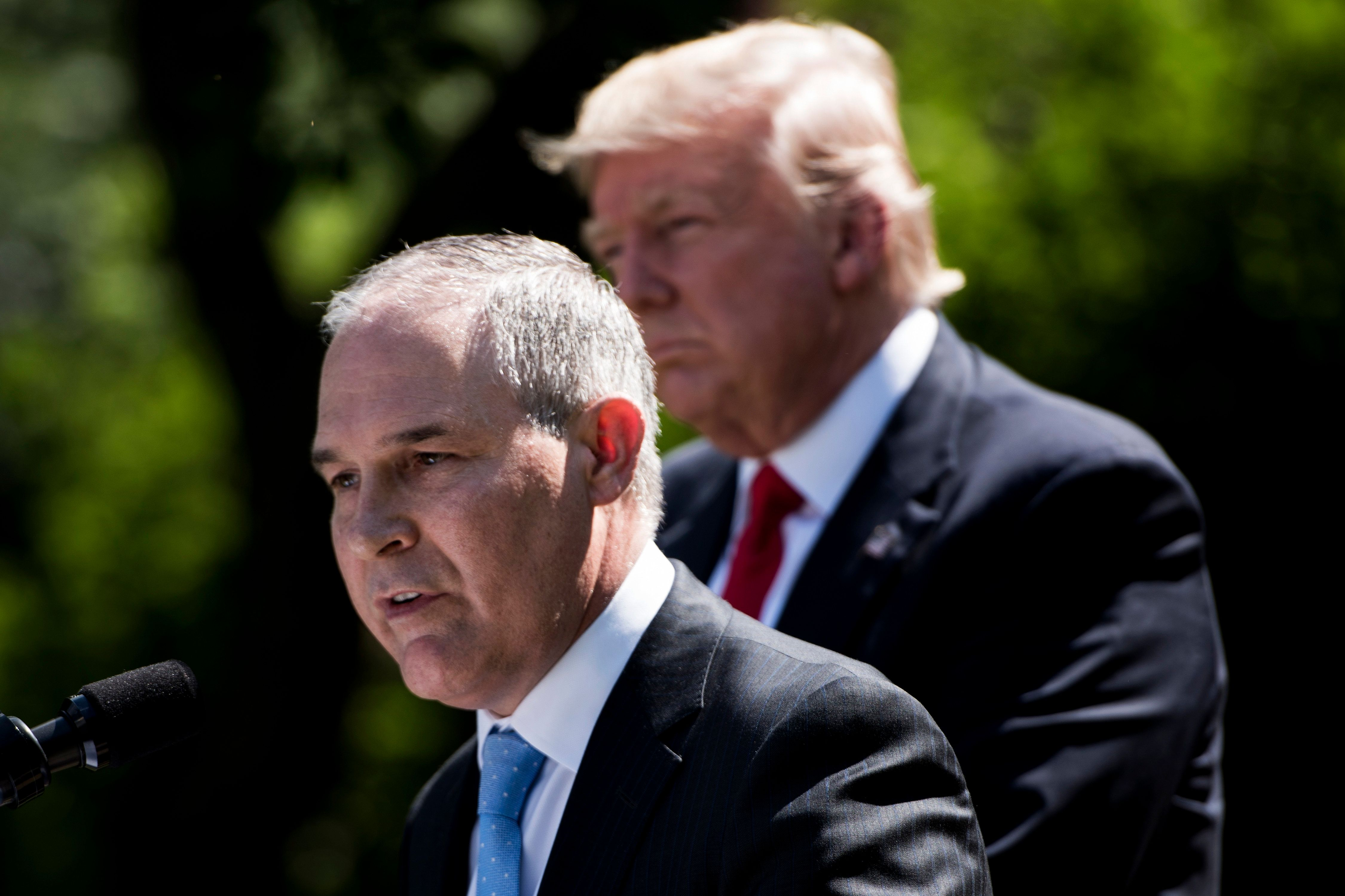 US President Donald Trump (R) listens while Environmental Protection Agency Administrator Scott Pruitt speaks after announcing the US will withdraw from the Paris accord in the Rose Garden of the White House June 1, 2017 in Washington, DC. 'As of today, the United States will cease all implementation of the non-binding Paris accord and the draconian financial and economic burdens the agreement imposes on our country,' Trump said. / AFP PHOTO / Brendan Smialowski        (Photo credit should read BRENDAN SMIALOWSKI/AFP/Getty Images)