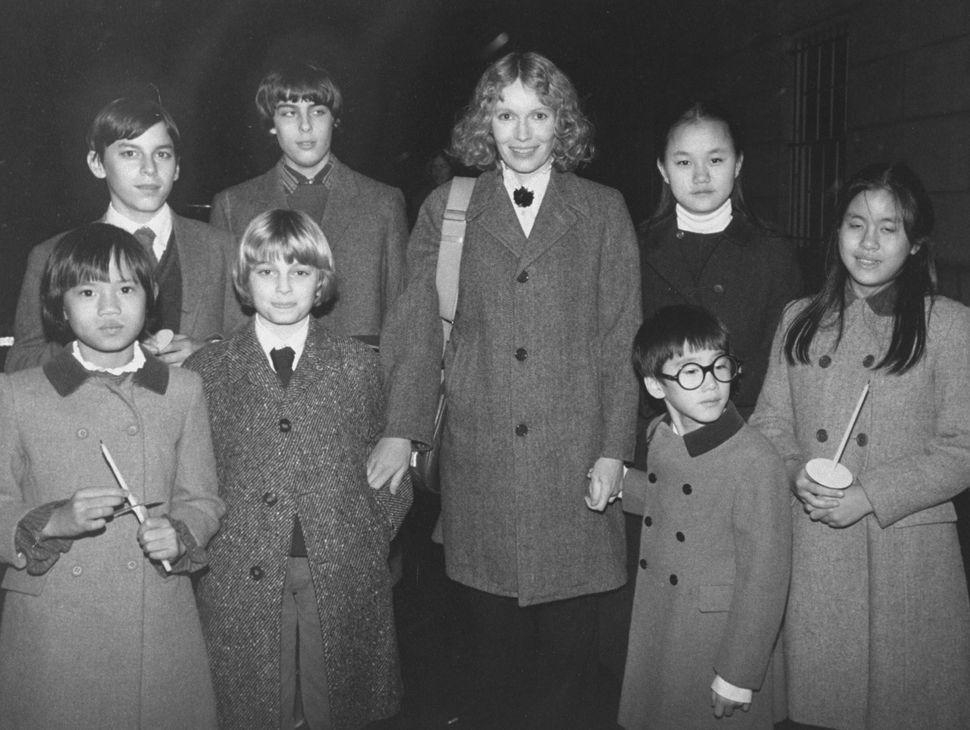 O Moses Farrow κάτω δεξιά, φορώντας γυαλία και κρατώντας το χέρι της μητέρας του, Mia Farrow.