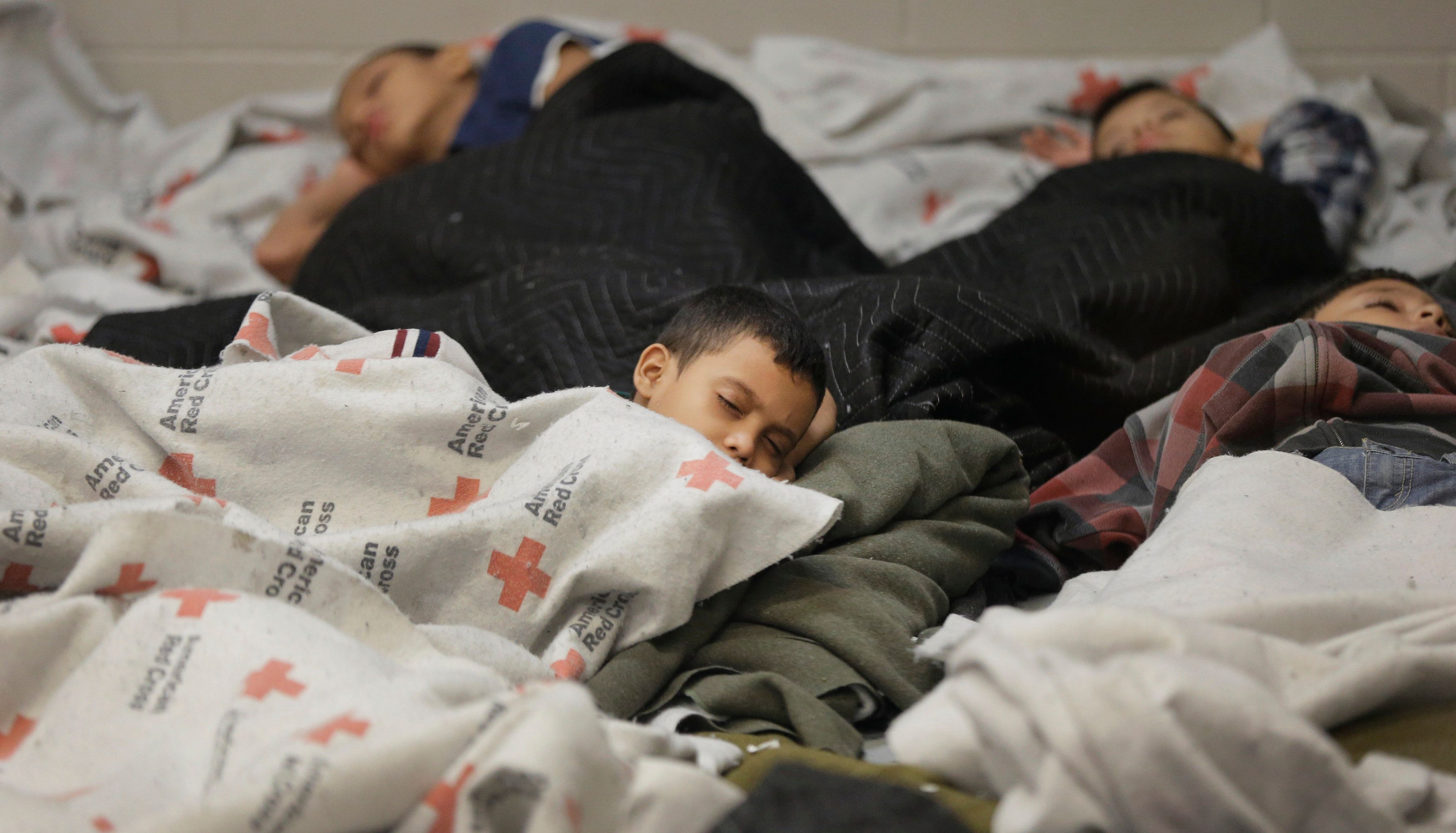 Detainees sleep in a holding cell at a U.S. Customs and Border Protection processing facility, in Brownsville, Texas June 18, 2014. CPB provided media tours June 18 of two locations in Brownsville and Nogales, Arizona that have been central to processing the more than 47,000 unaccompanied children who have entered the country illegally since Oct. 1.  REUTERS/Eric Gay/Pool  (UNITED STATES - Tags: CRIME LAW POLITICS SOCIETY)