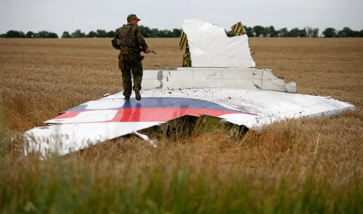 An armed pro-Russian separatist stands on part of the wreckage of the Malaysia Airlines Boeing 777 plane after it crashed nea