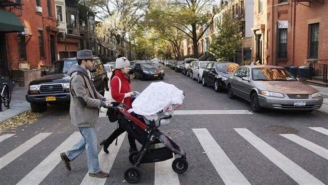 A couple with a baby stroller cross the street in the Park Slope neighborhood of Brooklyn. Between 2016 and 2017, about 51,00