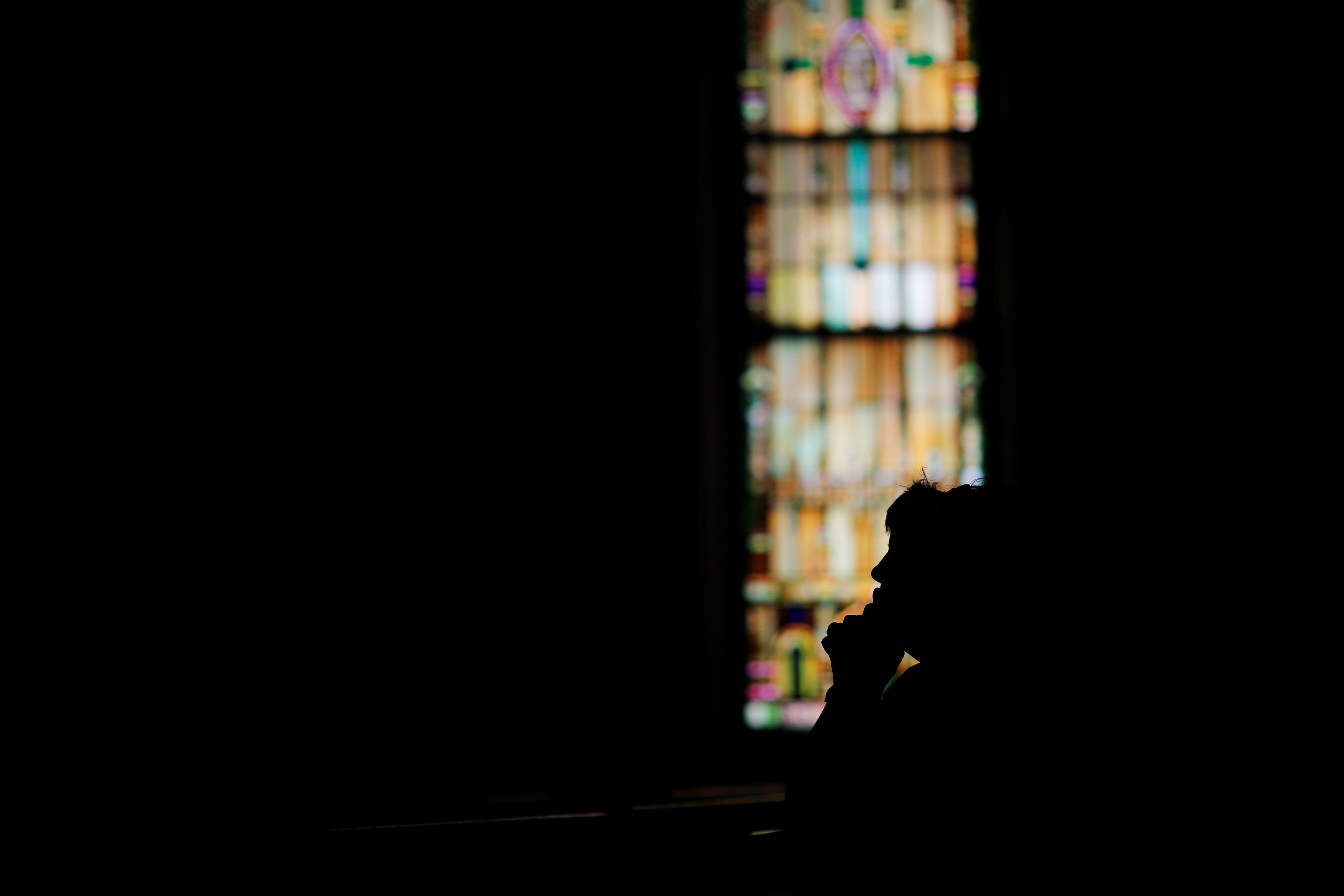 A woman prays at St. John's Church during a procession to carry a cross between the Catholic Churches of Quincy, Massachusetts, U.S., to pray the Stations of the Cross on Good Friday April 14, 2017. REUTERS/Brian Snyder