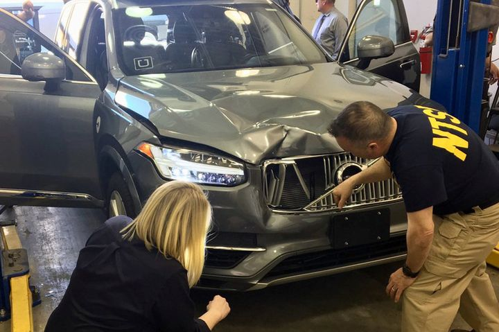 National Transportation Safety Board investigators examine the self-driving Uber vehicle involved in the fatal accident.