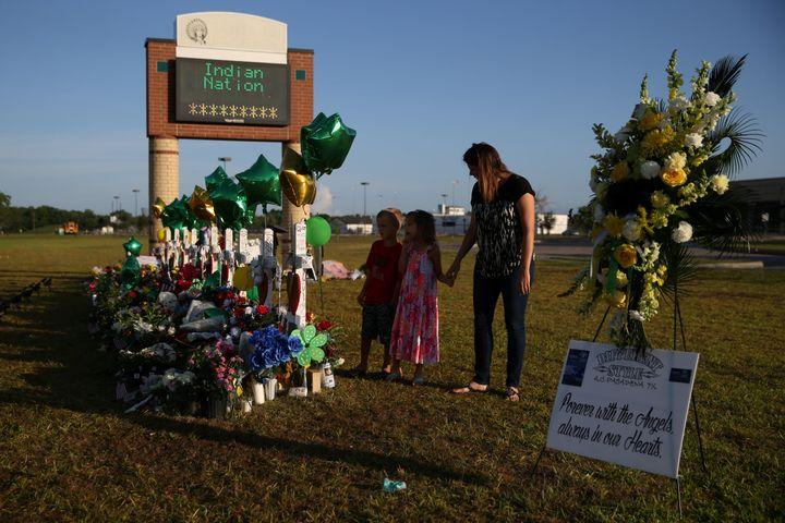 A woman and her children pay respects at a makeshift memorial at Santa Fe High School in Santa Fe, Texas, May 23, 2018. Survi