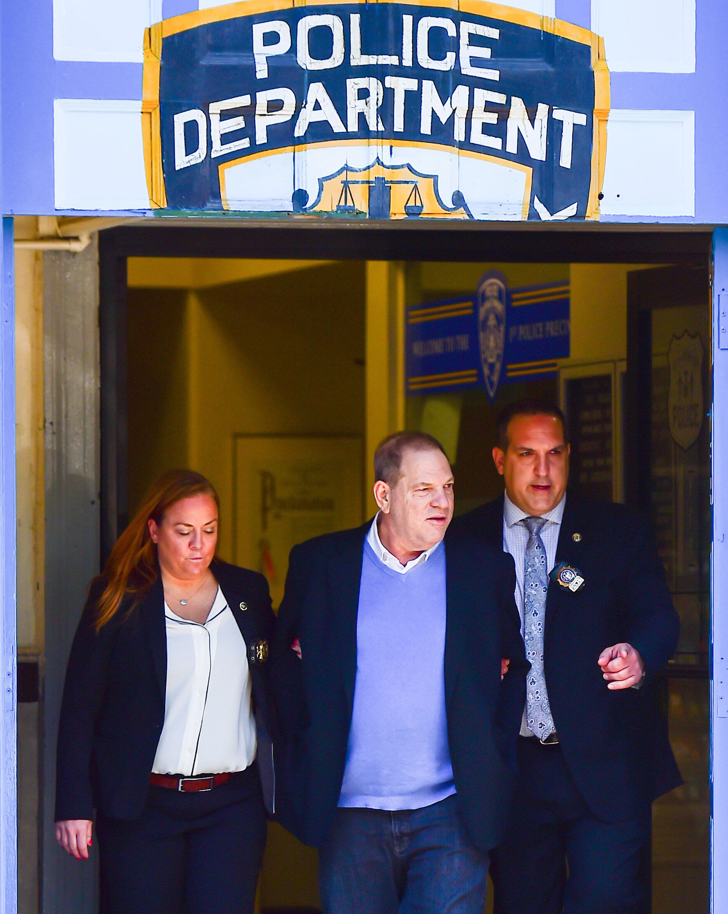 Harvey Weinstein is escorted out of the New York Police Department's First Precinct in handcuffs after turning himself in on Friday