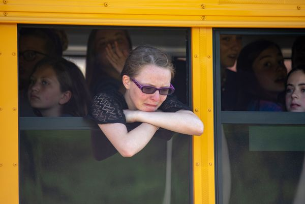 Evacuated middle school students wait on a bus outside Noblesville High School.