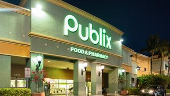 Publix food and pharmacy store facade in Miami at night, illuminated with a car approaching.