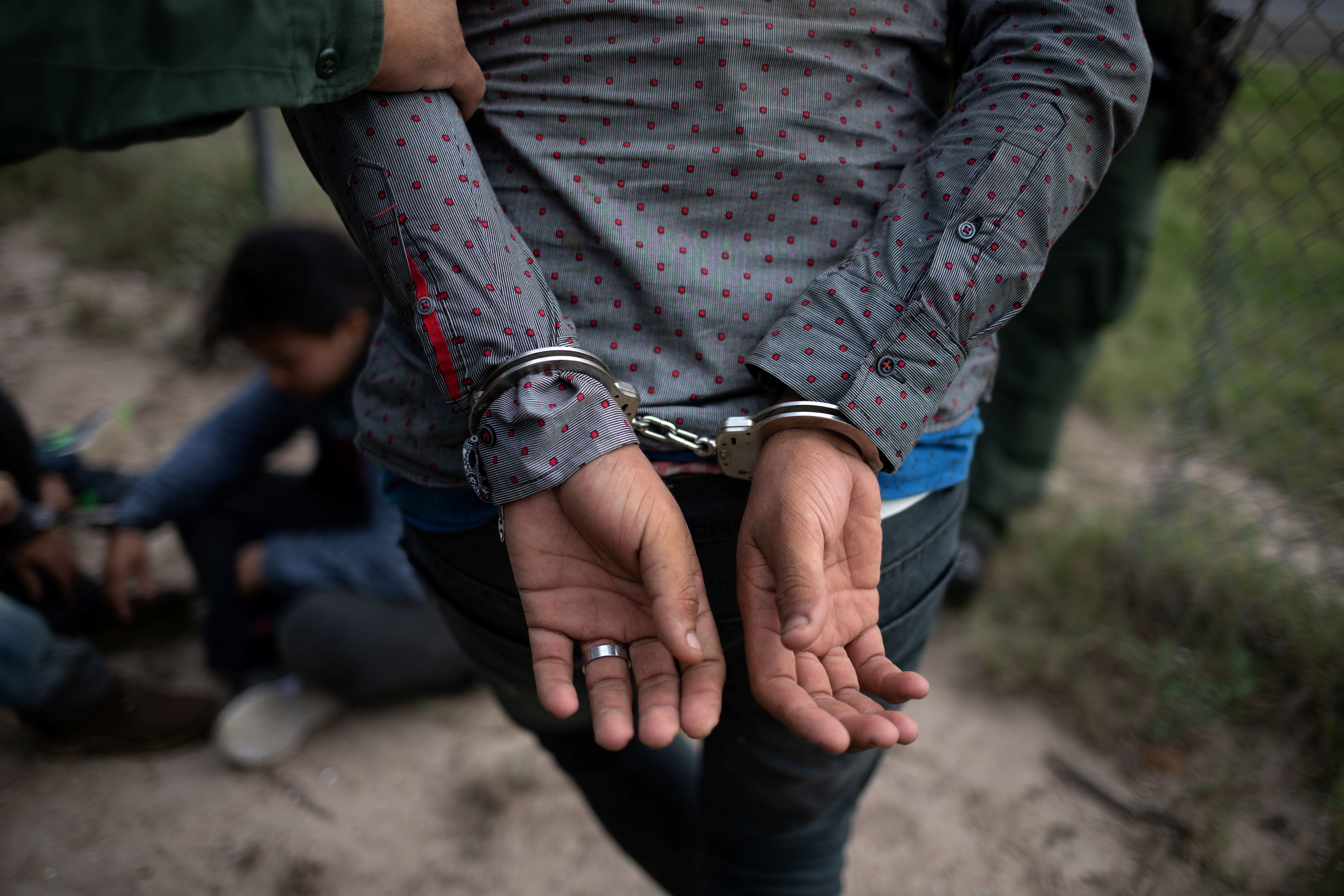 A border patrol agent apprehends a man after he and others were caught illegally crossing into the U.S. border from Mexico near McAllen, Texas, U.S., May 2, 2018.  REUTERS/Adrees Latif