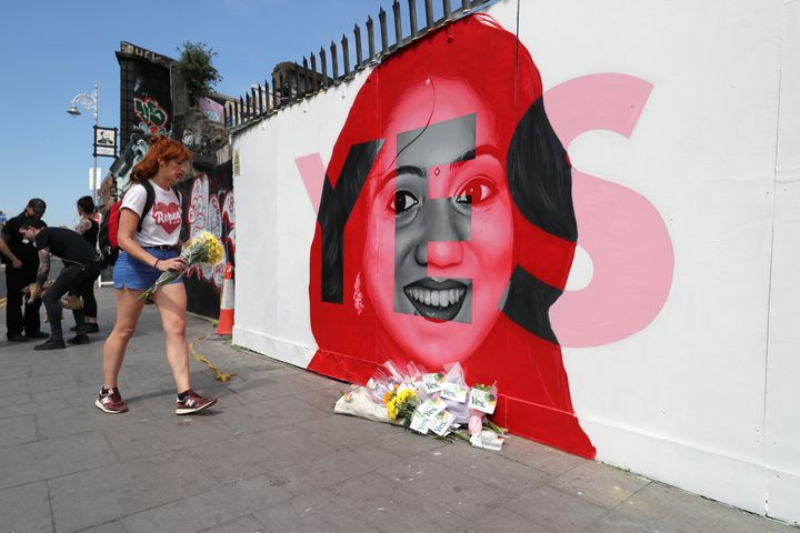 A woman lays flowers next to a mural of Savita Halappanavar in Dublin, as Ireland went to the polls. Savita lost her life after a miscarriage in a Galway hospital.