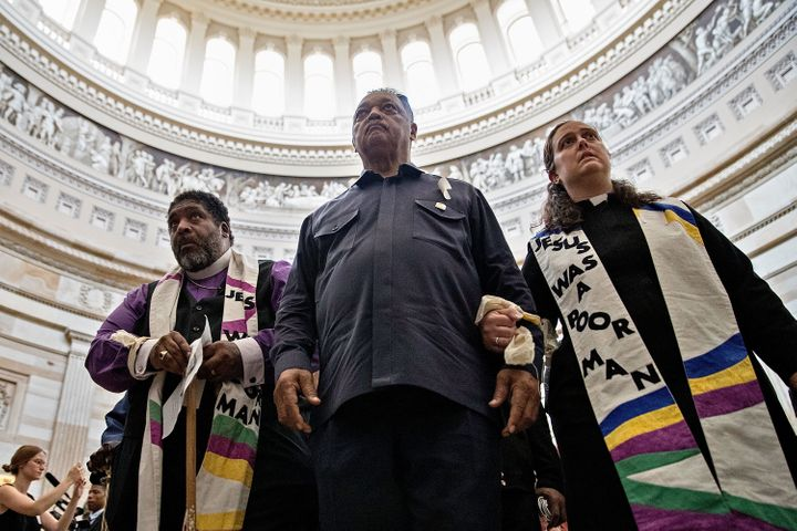 The Rev. William Barber, the Rev. Jesse Jackson and the rev. Liz Theoharis lead protesters through the U.S. Capitol Rotunda b
