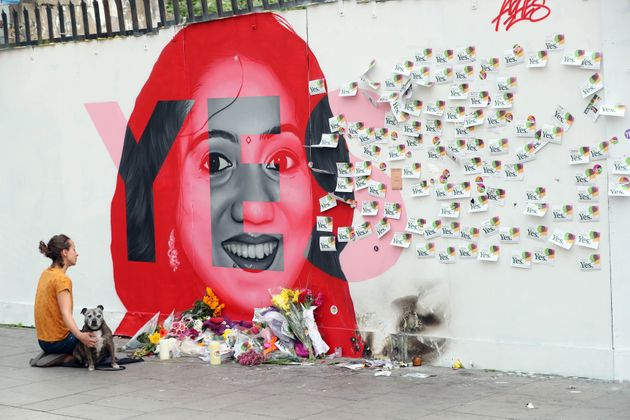 A woman kneels infront of a mural of Savita Halappanavar in