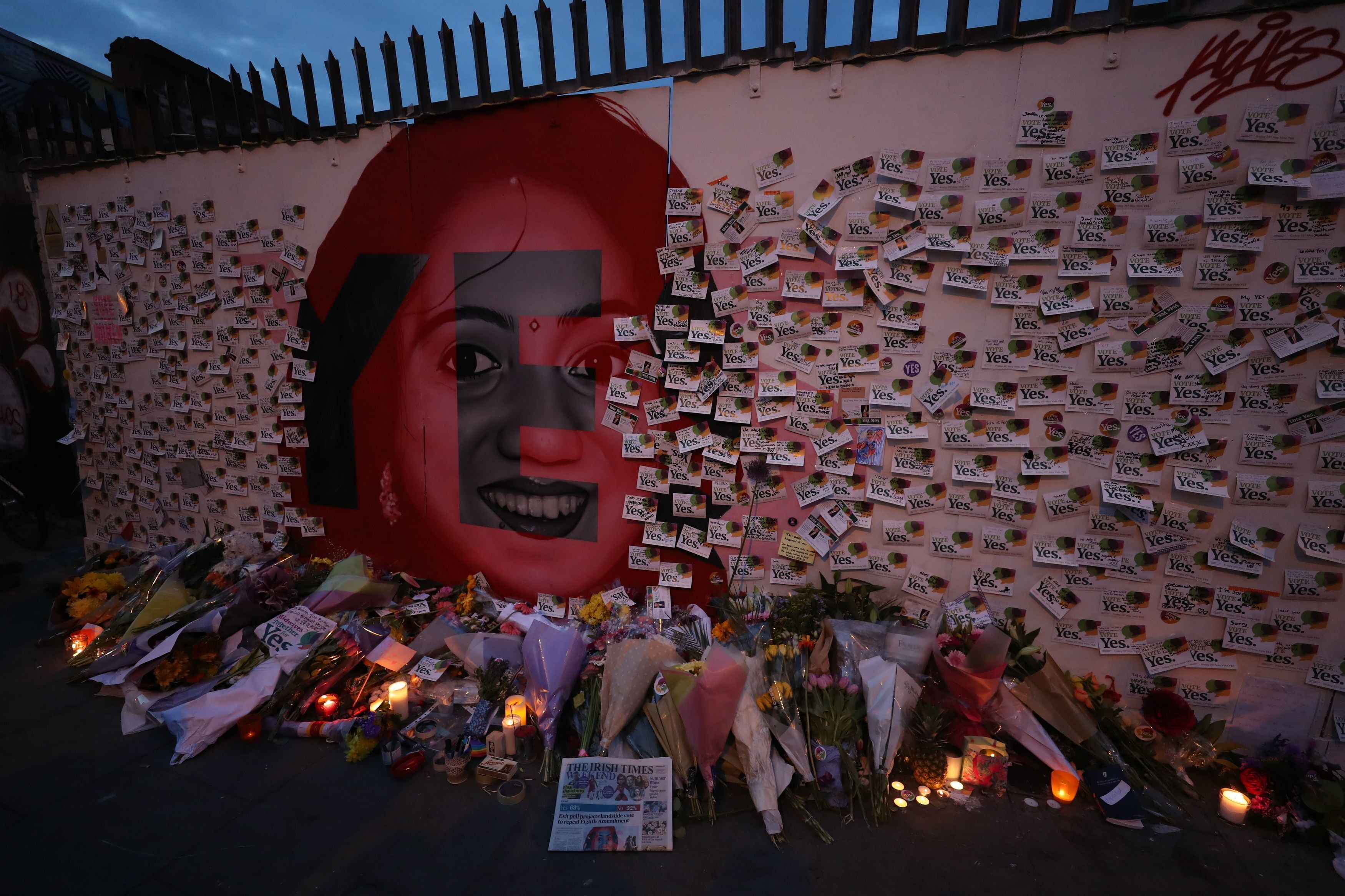 Niall Carson- PA Images via Getty Images                   Candle and flowers are placed in front of a mural of Savita Halappanavar in Dublin