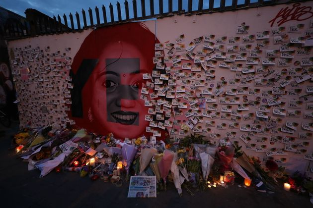 Candle and flowers are placed in front of a mural of Savita Halappanavar in