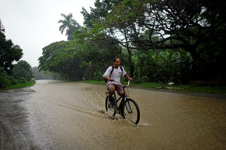 A man rides a bicycle down a flooded road in Bahia Honda, Cuba, as Subtropical Storm Alberto passes by the Caribbean island's