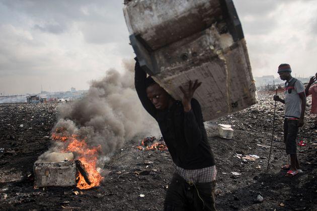 Ein junger Mann trägt einen alten Kühlschrank über eine Müllhalde inAgbogbloshie...