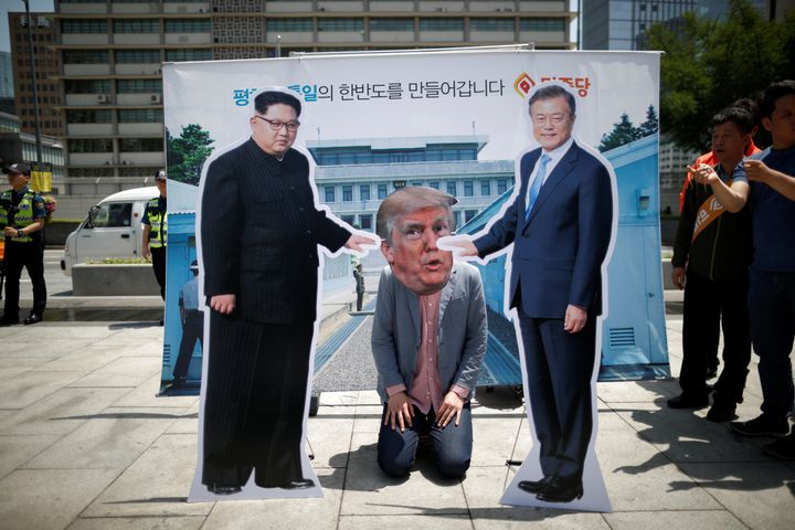 A man wearing a Trump mask kneels between cutouts of North Korean leader Kim Jong Un and South Korean President Moon Jae-in d