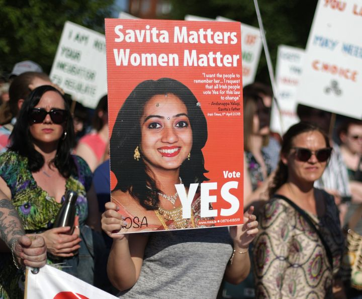 A woman holds a poster of Savita Halappanava at Belfast City Hall.
