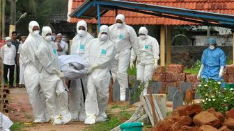 Doctors and relatives wearing protective gear carry the body of a victim, who lost his battle against the brain-damaging Nipah virus, during his funeral at a burial ground in Kozhikode, in the southern Indian state of Kerala, India, May 24, 2018. REUTERS/Stringer