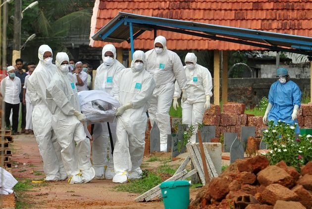 Doctors and relatives wearing protective gear carry the body of a victim of the brain-damaging Nipah...