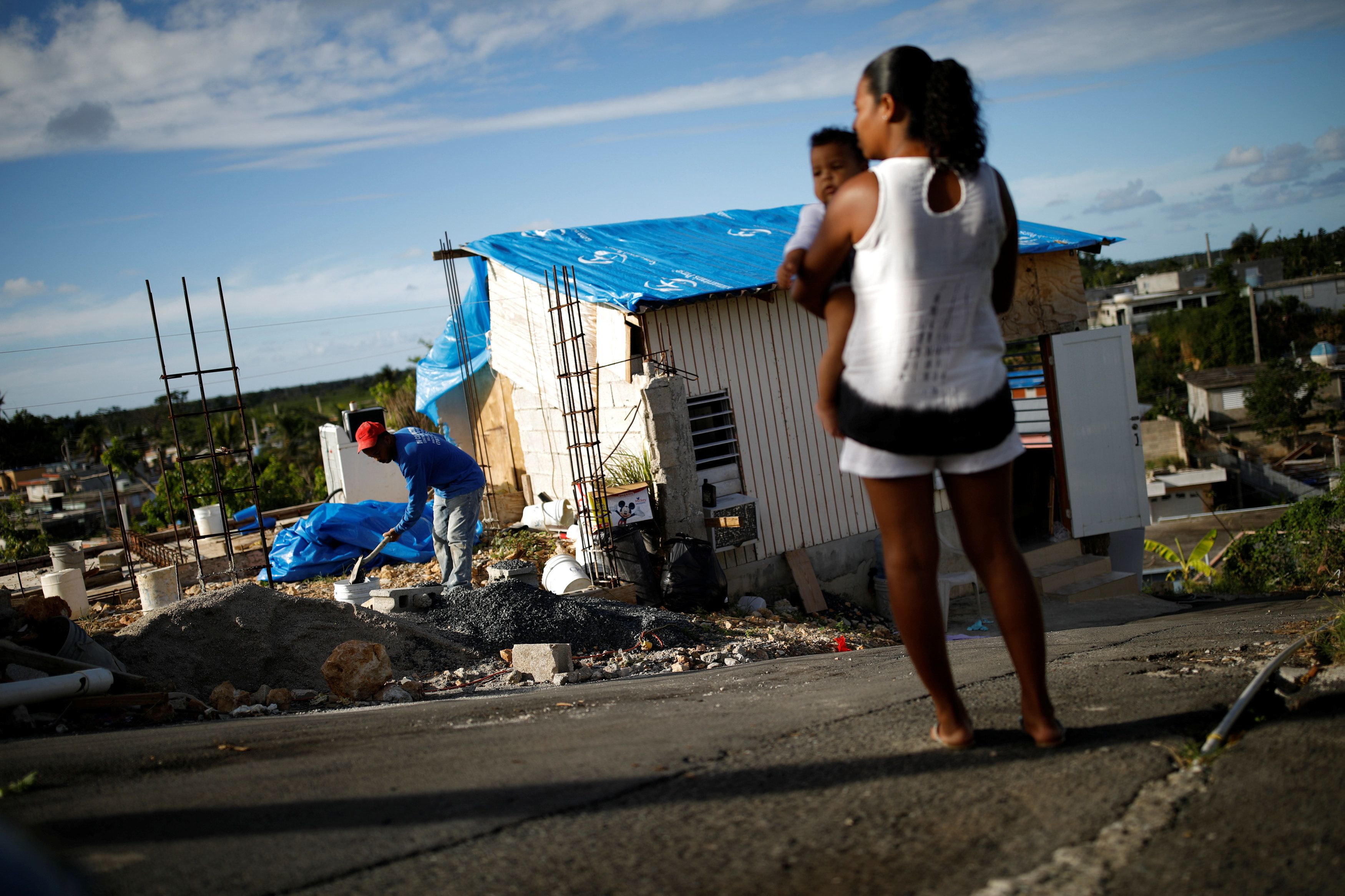 """Samuel Vasquez rebuilds his house, which was partially destroyed by Hurricane Maria, while his wife Ysamar Figueroa looks on, whilst carrying their son Saniel, at the squatter community of Villa Hugo in Canovanas, Puerto Rico, December 11, 2017. Villa Hugo is a settlement initially formed by people whose houses were damaged or destroyed by Hurricane Hugo in 1989. REUTERS/Carlos Garcia Rawlins  SEARCH """"RAWLINS HUGO"""" FOR THIS STORY. SEARCH """"WIDER IMAGE"""" FOR ALL STORIES."""