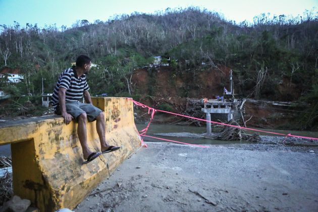 A man sits on the edge of a broken bridge spanning the Vivi River on Oct. 20, 2017 in Utuado, Puerto