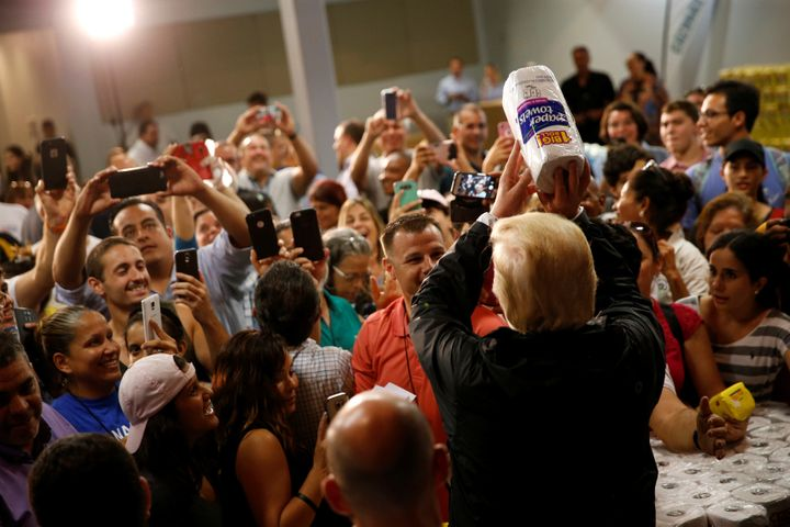 U.S. President Donald Trump bizarrely tosses rolls of paper towels to people at a hurricane relief distribution center at Cal