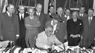 6/22/1944-Washington, DC-ORIGINAL CAPTION READS: President Roosevelt today signed the 'G.I.Bill of Rights' which provides broad benefits for veterans of World War II.The ceremony was witnessed by members of the Senate and House and members of the American Legion and Veterans of Foreign Wars.L to r front row in rear of President:Sen.Bennett Champ Clark of MO, Cong.J.Hardin Peterson of FL, Cong.John R.Frankin of MS, Edith Nourse Rogers of MA.Leaning back over the President:Sen.Walter F.George of GA. Back of Mrs.Rogers:Sen.Robert F.Wagner of NY,and Sen.Alben Barkley of KY.