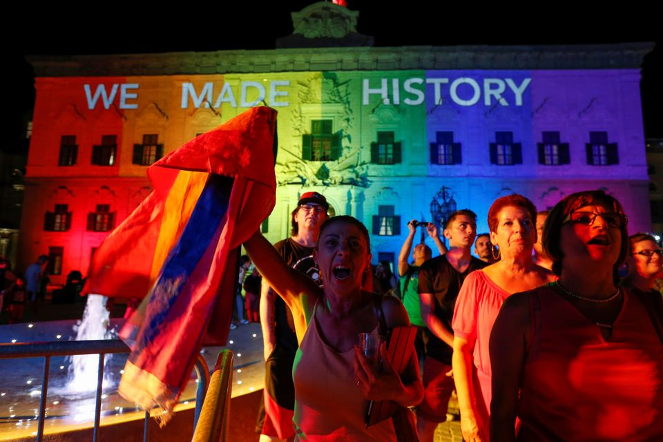 People celebrate in front of the rainbow-colour lit Auberge de Castille, the office of Prime Minister Joseph Muscat, after th