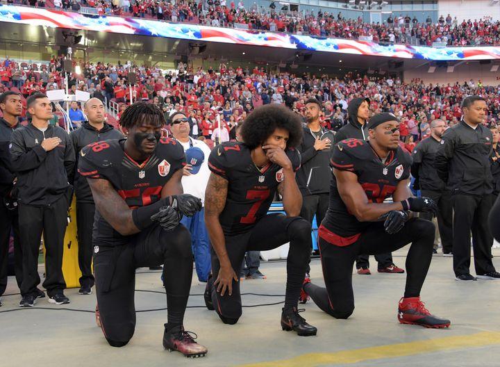 San Francisco 49ers outside linebacker Eli Harold (58), quarterback Colin Kaepernick (7) and free safety Eric Reid (35) kneel