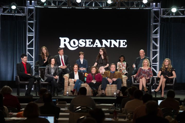 "Roseanne Barr sits front and center with the cast of her now-canceled reboot, ""Roseanne."""