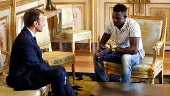 French President Emmanuel Macron (L) speaks with Mamoudou Gassama, 22, from Mali, at the presidential Elysee Palace in Paris, on May, 28, 2018. - Mamoudou Gassama living illegally in France is being honored by Macron for scaling an apartment building over the weekend to save a 4-year-old child dangling from a fifth-floor balcony. (Photo by Thibault Camus / POOL / AFP)        (Photo credit should read THIBAULT CAMUS/AFP/Getty Images)