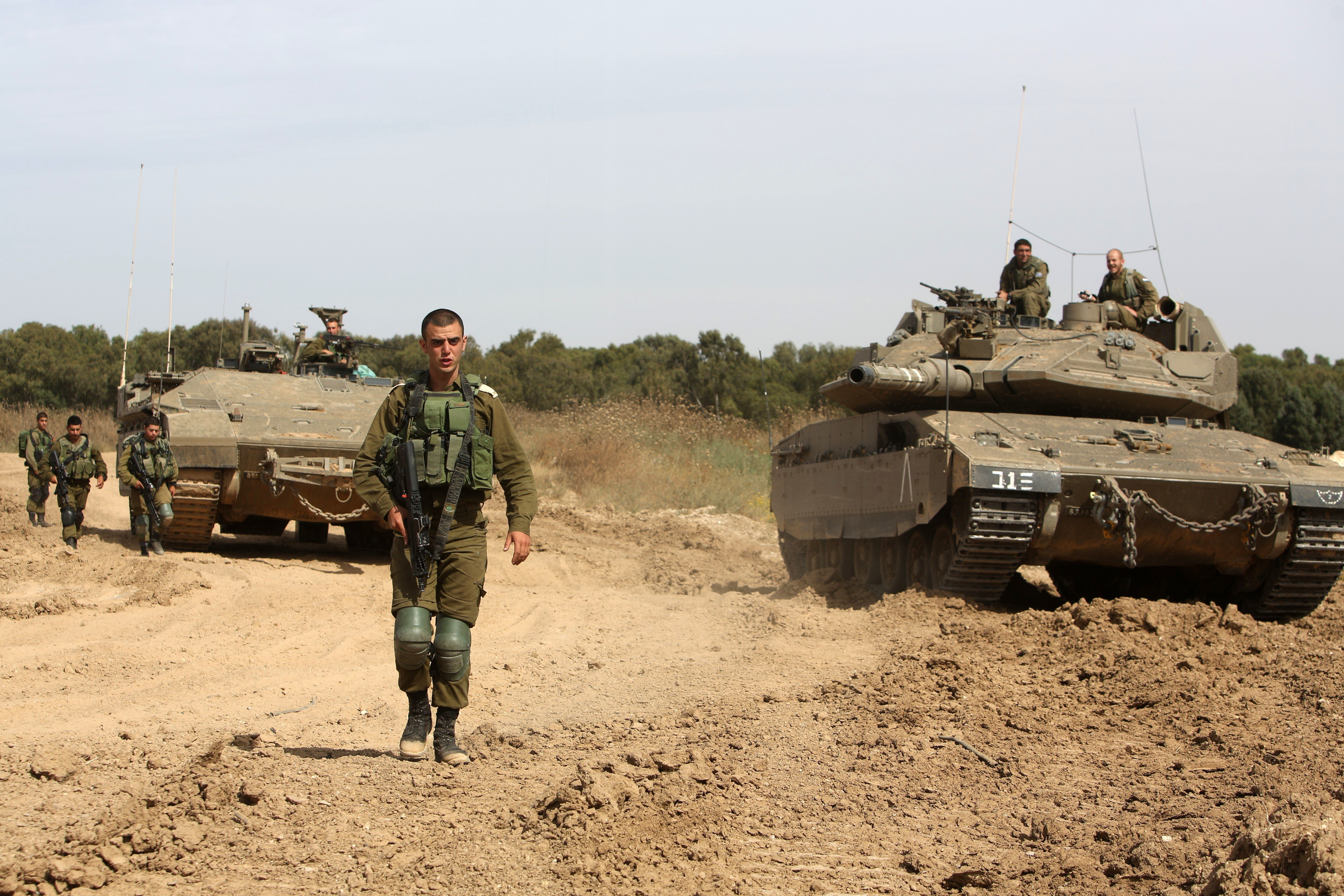 Israeli soldiers stand guard next to a tank and an APC (armoured personal carrier) along the border between Israel and the Gaza Strip near the southern Israeli Kibbutz of Nahal Oz on May 4, 2016. The border between Israel and the Gaza Strip saw a bout of violence, with exchanges of fire that put a 2014 ceasefire agreement to the test. Israeli tanks fired into the Hamas-run Palestinian enclave at least twice, saying it was in response to mortar fire across the border, while the army designated an Israeli border town a closed military zone.   / AFP PHOTO / MENAHEM KAHANA        (Photo credit should read MENAHEM KAHANA/AFP/Getty Images)