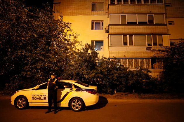 A Ukrainian police officer guards near an apartment block where Russian journalist Arkady Babchenko was
