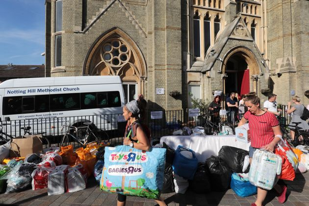 People leave donations outside the Notting Hill Methodist Church near the burning 24 storey residential...