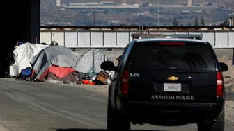 Police continue their patrols as officials begin what they are calling a slow and methodical clean-up and removal of a large homeless encampment along the Santa Ana River Trail in Anaheim, California, U.S., January 22, 2018.      REUTERS/Mike Blake