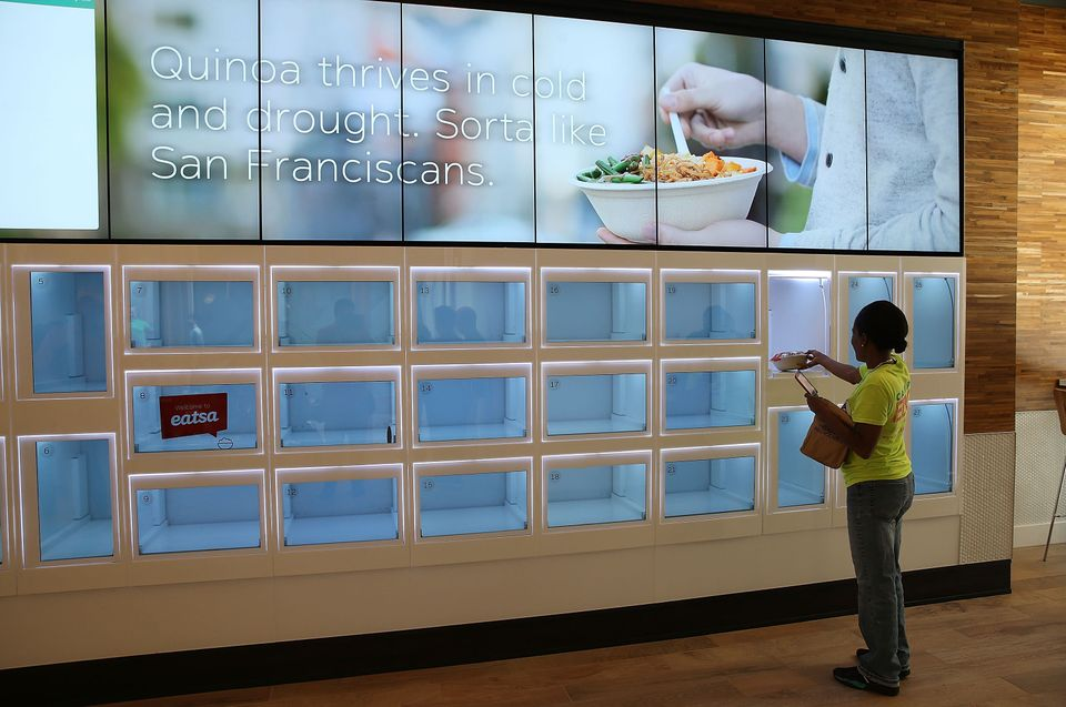 A customer picks up her food from a cubby at Eatsa, a largely automated restaurant in San