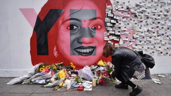 DUBLIN, IRELAND - MAY 26: A young woman leaves flowers at the Savita Halappanavar mural as the results in the Irish referendum on the 8th amendment concerning the country's abortion laws takes place at Dublin Castle on May 26, 2018 in Dublin, Ireland.  Savita Halappanavar who became the symbol of the Yes campaign to repeal the 8th amendment, died aged 32, due to complications following a septic miscarriage in Galway in 2012. Voters in Ireland went to the polls yesterday to decide whether to abolish or keep the 8th amendment, which makes it illegal for a woman to have an abortion in the country unless in circumstances where her life is at risk. Exit polls have indicated that the Yes vote has won by a landslide majority. (Photo by Charles McQuillan/Getty Images)