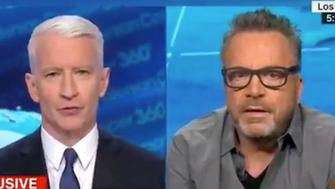 Tom Arnold right being interviewed by Anderson Cooper about the cancellation of Roseanne