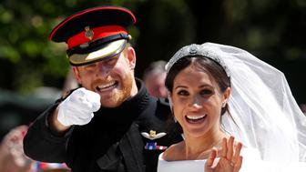 Britain's Prince Harry gestures next to his wife Meghan as they ride a horse-drawn carriage after their wedding ceremony at St George's Chapel in Windsor Castle in Windsor, Britain, May 19, 2018. REUTERS/Damir Sagolj