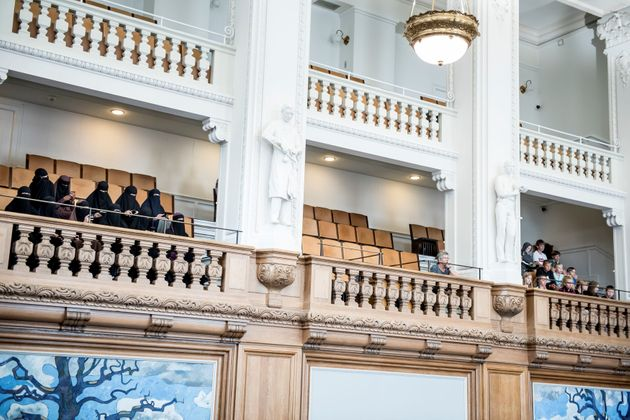Women in niqabs observe the Danish Parliament as it bans face veils in public in a vote Thursday at Christiansborg...