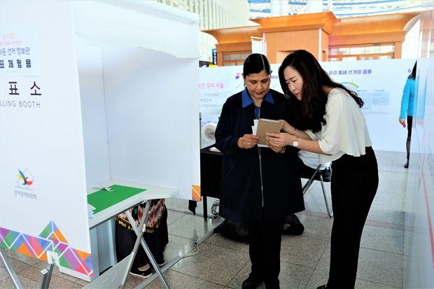 서울시선관위 직원이 아름다운 선거 정보관에서 볼리비아 이주여성에게 투표방법을 안내해 주고