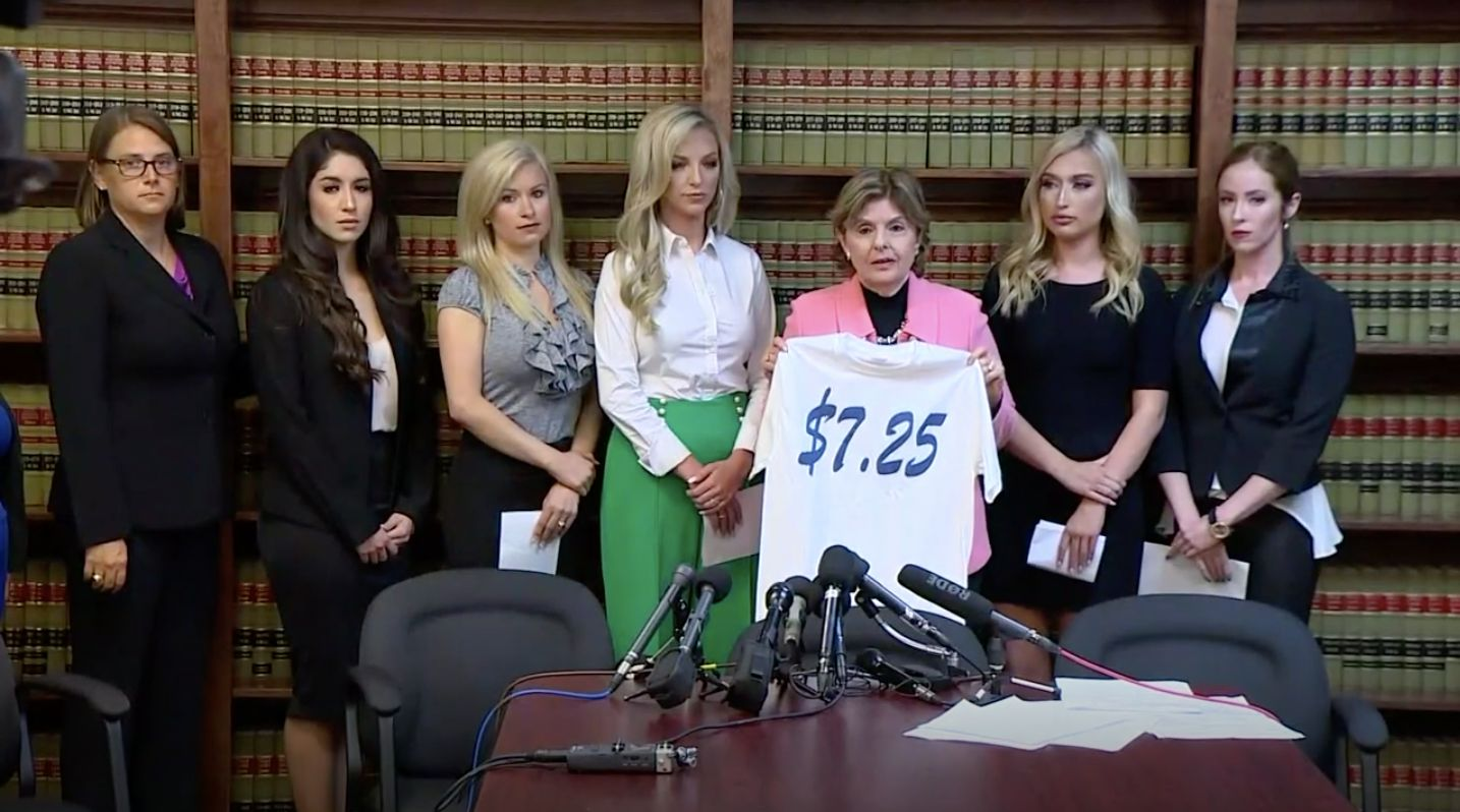 Gloria Allred, holding a T-shirt featuring the federal minimum wage, is flanked by five former Texans cheerleaders