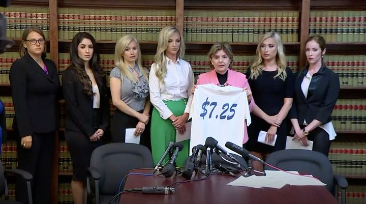 Gloria Allred, holding a T-shirtfeaturing the federal minimum wage, is flanked by fiveformer Texans cheerleaders