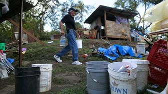 Angel Colon carries containers with water as he walks past a little hut, in which he lives since his house was destroyed during Hurricane Maria in September 2017, in Comerio, Puerto Rico January 31, 2018. Picture taken January 31, 2018. REUTERS/Alvin Baez