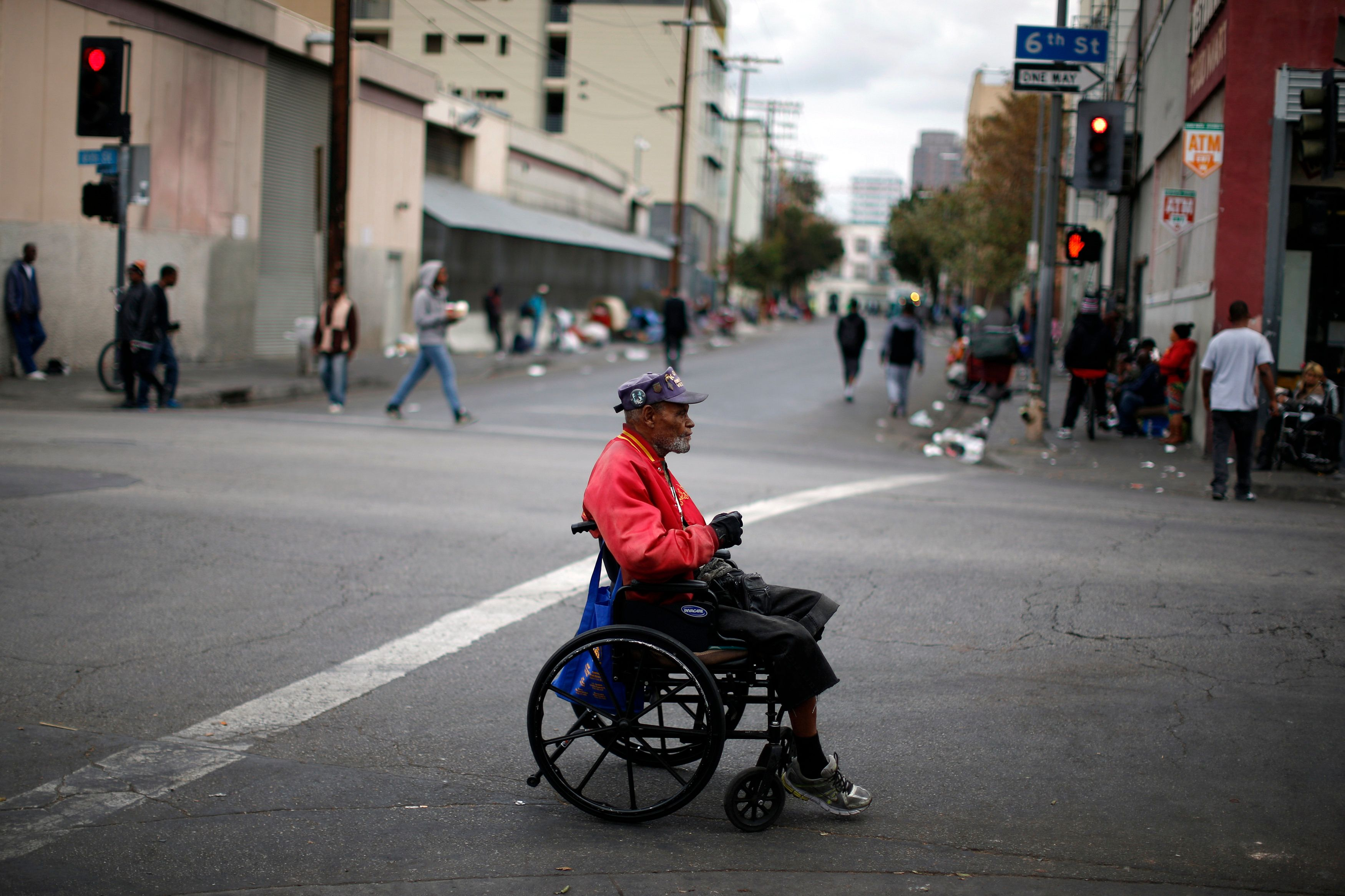 Homeless U.S. marine corps Korean War veteran Arthur Turner, 79, crosses the road on skid row in Los Angeles after a Veterans Day observance for homeless veterans at The Midnight Mission shelter, California November 11, 2014. REUTERS/Lucy Nicholson   (UNITED STATES - Tags: MILITARY)